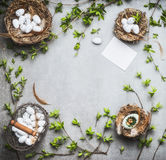 Easter frame background. Nest and basket with eggs , spring twigs and leaves , top view Royalty Free Stock Image