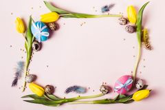 Easter Frame of beautiful yellow tulips, decorated eggs and beads. Holiday mock up royalty free stock photography