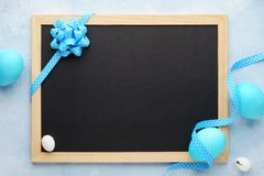 Easter frame with blue eggs and empty chalkboard. Easter frame with painted blue eggs and empty chalkboard. Background with copy space royalty free stock photography