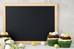 Easter frame chalkboard background with cupcakes and flowers stock images