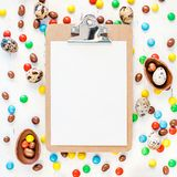 Easter frame with chocolate eggs, colorful candies. Creative Top view flat lay holiday composition Easter quail, chocolate eggs, colorful candies on white wooden royalty free stock photo