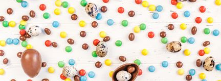 Easter frame with chocolate eggs, colorful candies. Creative Top view flat lay holiday composition Easter quail, chocolate eggs, colorful candies on white wooden royalty free stock photos