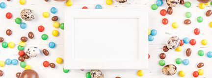 Easter frame with chocolate eggs, colorful candies. Creative Top view flat lay holiday composition Easter quail, chocolate eggs, colorful candies on white wooden stock photography