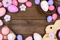 Easter frame with eggs, bunny and flowers on rustic wood Royalty Free Stock Photos