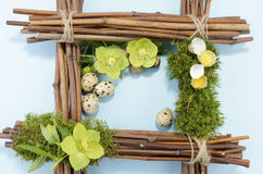 Easter frame with one boiled quail egg in the right corner and two raw plus three hellebore flowers Royalty Free Stock Photography