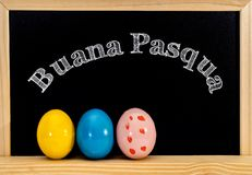 Easter frame with painted eggs and chalkboard. Happy Easter in white chalk. Happy Easter in italian : buana pasqua stock photo
