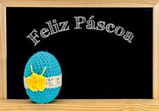 Easter frame with painted eggs and chalkboard. Happy Easter in white chalk. Happy Easter in portuguese : feliz páscoa stock image
