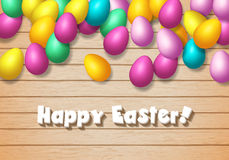 Easter frame with shiny colorful happy eggs spread over wooden b. Easter frame with shiny colorful eggs spread over wooden background Royalty Free Stock Image