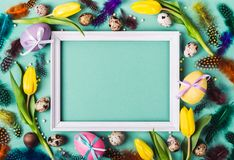 Easter Frame of yellow tulips, decorated eggs and feathers on turquoise background for greeting message.  stock image