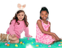 Easter friends. Two girls sitting with Easter eggs on green holiday grass Stock Images