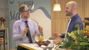 Easter fun at office. Business people playing with Easter eggs, gestures, elegant business style, bunny table decoration, funny tradition, men talking over table