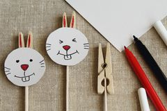 Easter. Funny, cunning hares from wooden clothes pegs, a sheet of white cardboard and colored felt-tip pens on sackcloth stock images