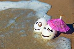 Easter funny eggs under umbrella on a beach Stock Photos