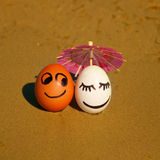 Easter funny eggs under umbrella on a beach Stock Images