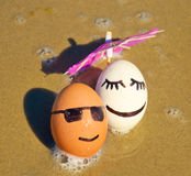 Easter funny eggs under umbrella on a beach Stock Photos