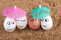 Easter funny eggs under umbrella on a sand Stock Photo