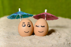 Easter funny eggs under umbrella Stock Photos