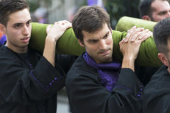 Easter in Galicia Spain. PONTEVEDRA, SPAIN - APRIL 2, 2015: Members of a religious brotherhood carrying a heavy religious image, parading in a procession in Royalty Free Stock Photography