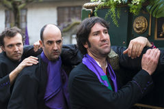 Easter in Galicia Spain. PONTEVEDRA, SPAIN - APRIL 2, 2015: Members of a religious brotherhood carrying a heavy religious image, parading in a procession in Royalty Free Stock Images