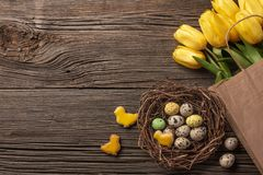 Easter gingerbread cookies on wooden table and yellow tulips. Greeting card. Top view with copy space.  stock image