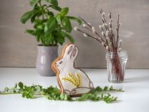 Easter gingerbread, fresh basil in a ceramic pot and a small bouquet of rosewood branches. On a white table royalty free stock photography