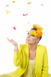 Easter girl. Picture of an easter girl dressed in yellow, with eggs in her hair, feathers falling down, on a white, isolated background Royalty Free Stock Photos