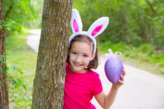 Easter girl with big purple egg and funny bunny ears. On the forest stock images