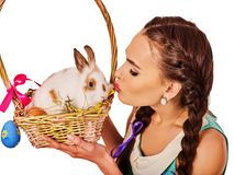 Woman in easter style holding eggs and flowers. Easter girl holding bunny and eggs. Holiday style holding and group of rabbits in basket with flowers. Spring Stock Photos