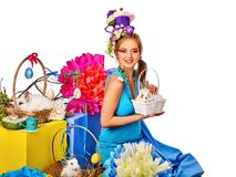 Woman in easter style holding rabbit and flowers in basket. Easter girl holding bunny and eggs. Spring woman with holiday hairstyle and make up holding rabbit Royalty Free Stock Photo