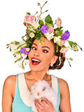 Easter girl holding bunny. Woman with holiday spring flowers hairstyle. Stock Image