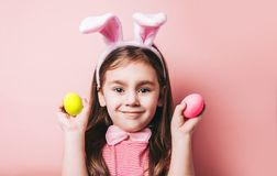 Cute little girl with bunny ears on pink background. Easter girl portrait. Cute little girl with bunny ears on pink background. Easter child portrait, funny stock images