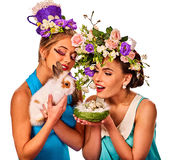 Easter girl together holding bunny. Women in holiday style. Easter girl together holding bunny. Women in holiday style celebrate take rabbits with and a basket Stock Images