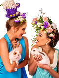 Easter girl together holding bunny. Women in holiday style. Easter girl together holding bunny. Women in holiday style celebrate take rabbits with flowers Royalty Free Stock Image