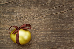 Easter golden egg with a brown ribbon. Stock Photos