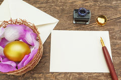 Easter golden egg near the pen. Royalty Free Stock Image