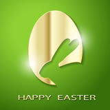 Easter Golden Egg silhouette of a Rabbit on a green background. Stock Image