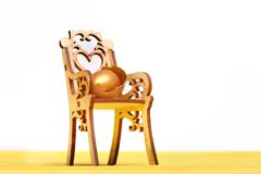 Easter golden egg on wooden chair, future life, healthy food. Hapyy easter holidays eggs and bunny wooden chair with golden egg in broken shell, easter food Stock Photography