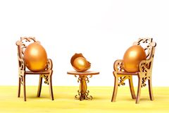 Easter golden egg on wooden chair at table, future life. Happy easter egg. holiday bunny and eggs, spring flower backround golden eggs in broken shell, easter Stock Photo