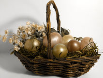 Easter - Golden Eggs. Easter basket with flowers and eggs, gold tone royalty free stock photo