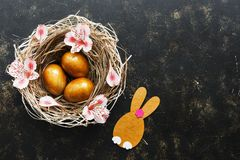 Easter golden eggs and a rabbit in a nest decorated with pink flowers on a brown dark background. Top view, place for text.  royalty free stock image