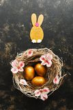 Easter golden eggs and a rabbit in a nest decorated with pink flowers on a brown dark background. Top view, place for text.  royalty free stock photo