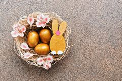 Easter golden eggs and a rabbit in a nest decorated with pink flowers on a brown stone background. Top view, place for text.  stock photo