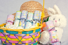 Easter Goodies. An image showing the concept of easter with a bunny, a bonnet and a basketful of crackers Stock Photo