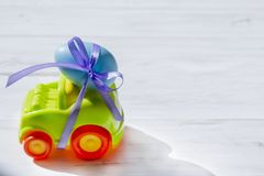 Easter green cars with a blue egg. Easter light green car with a blue egg tied with a purple ribbon rides on the table stock image