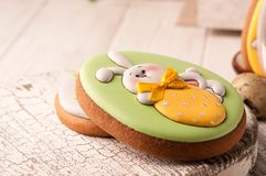 Easter green cookie with painted easter bunny holding yellow strawberry royalty free stock image