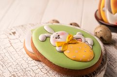 Easter green cookie with painted easter bunny holding yellow strawberry on white cutting boards stock photo