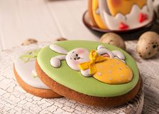 Easter green cookie with painted easter bunny in yellow bow holding strawberry stock photography
