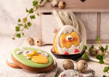 Easter green cookies with painted easter bunny and hatched chicken in bowl near quail eggs, decorative sideboard royalty free stock photos