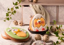 easter green cookies with painted easter bunny and hatched chicken in bowl near quail eggs, decorative sideboard and napkin royalty free stock image