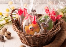 Easter green and yellow wrapped cookies in a brown wicker basket near stock photos